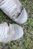 Пакостные старые ботинки на предпосылке травы, стиле натюрморта Стоковая Фотография