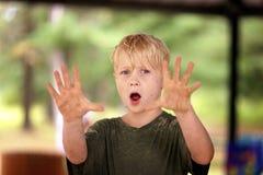 Пакостный мальчик предусматриванный в песке говоря нет и задерживая руки стоковая фотография