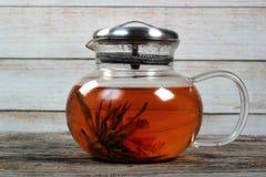 Пакостный стеклянный чайник с цветком чая на старом деревянном столе Стоковые Фотографии RF