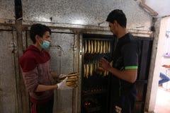 Палестинский человек подготавливает скумбрию куриться в Рафахе в южном секторе Газа стоковые фото