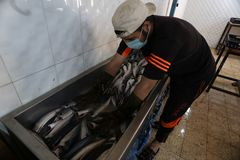 Палестинский человек подготавливает скумбрию куриться в Рафахе в южном секторе Газа стоковые изображения rf