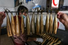 Палестинский человек подготавливает скумбрию куриться в Рафахе в южном секторе Газа стоковые изображения