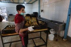 Палестинский человек подготавливает скумбрию куриться в Рафахе в южном секторе Газа стоковая фотография rf