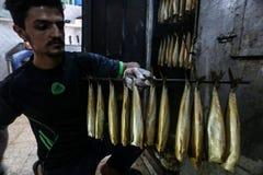 Палестинский человек подготавливает скумбрию куриться в Рафахе в южном секторе Газа стоковое изображение rf