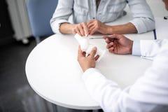 Палец женщины указывая на модель колена в руке доктора стоковое фото rf