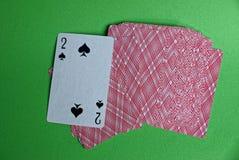 Палуба красных карточек с пиковым deuce на зеленой таблице стоковые фото