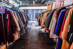 Пальто и куртки на вешалках в магазине Продажа outerwear стоковые изображения rf