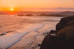 Пальто и океан с волнами на теплых заходе солнца или восходе солнца Lombok, Индонесия стоковая фотография rf