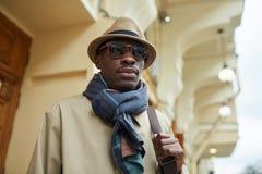 Пальто канавы африканского человека нося стоковое изображение rf