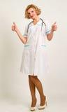 Пальто лаборатории доктора женщины нося белое держа 2 большого пальца руки вверх Стоковые Изображения RF