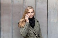 Пальто молодой женщины нося используя стену металла smartphone Стоковое Фото