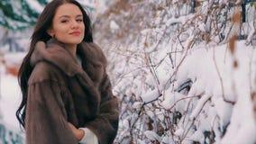 Пальто талии женщины брюнет богатое коричневого меха на предпосылке замедленного движения дерева видеоматериал