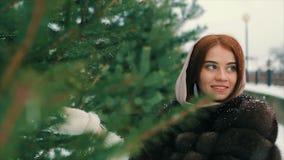 Пальто талии женщины брюнет богатое коричневого меха около замедленного движения рождественской елки видеоматериал