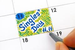 Пальцы женщины с напоминанием сочинительства ручки определяют день 11 11 в cal Стоковое Изображение