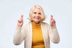 Пальцы кавказской женщины Enior усмехаясь пересекая с надеждой и глаза закрыли стоковое фото