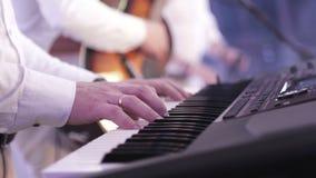 Пальцы музыканта которые играют на электронном синтезаторе во время концерта сток-видео