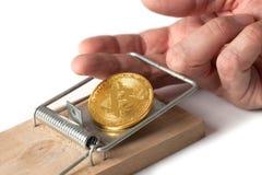 Пальцы поглощены в ловушке bitcoin изолированной на белизне стоковое фото