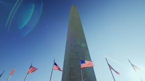 Памятник Вашингтона, солнечный пирофакел от флага который порхает в ветре акции видеоматериалы