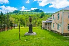 Памятник к Ленину на предпосылке зеленых гор Стоковое Фото