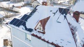 Панели солнечных батарей на крыше дома после сильного снегопада в зиме Стоковая Фотография