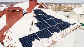 Панели солнечных батарей на крыше дома после сильного снегопада в зиме Стоковые Изображения
