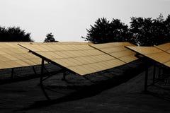 Панели солнечных батарей обрабатывают землю в поле в сельской местности с солнечностью раннего утра Стоковое Изображение RF