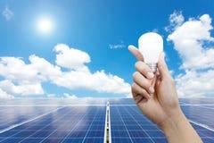 Панели и электрическая лампочка солнечной энергии в руке, энергии Стоковая Фотография RF