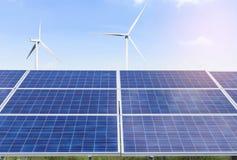 панели солнечных батарей и ветротурбины производя электричество в электростанции стоковое фото
