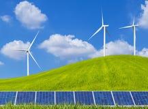 Панели солнечных батарей и ветротурбины Photovoltaics на зеленом поле Стоковые Изображения