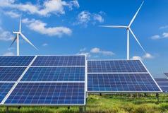Панели солнечных батарей и ветротурбины Photovoltaics производя электричество в станции солнечной энергии стоковые фото