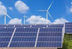 Панели солнечных батарей и ветротурбины Photovoltaics производя электричество в станции солнечной энергии стоковое фото