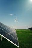Панели солнечных батарей и ветрянка производят электричество от солнца стоковое фото