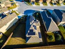 Панели солнечных батарей крыши воздушные над пригородным домом обеспечивая чистую устойчивую зеленую энергию Стоковые Изображения RF