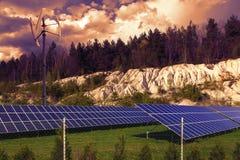 Панели солнечных батарей на зеленой траве на заходе солнца Стоковое фото RF