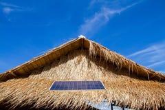 Панели солнечных батарей на крыше покрыванной соломой с сухими лист экологичность гловальная C Стоковое Фото