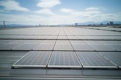 Панели солнечных батарей на крыше industial здания производят электричество стоковые изображения rf