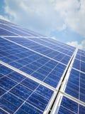 Панели солнечных батарей обрабатывают землю на красивой вертикали предпосылки голубого неба Стоковые Изображения