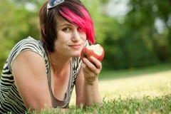 Панковская девушка есть яблоко Стоковые Изображения