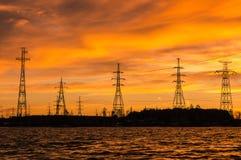 Панорама высоковольтных линий электропередач приближает к воде на заходе солнца стоковое изображение