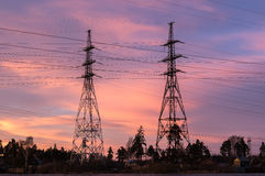 Панорама высоковольтных линий электропередач приближает к воде на заходе солнца стоковое фото rf