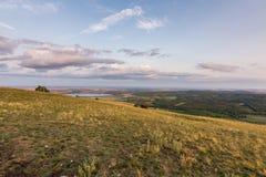 Панорама ландшафта захода солнца, холмы в золотом часе, малая деревня в долине, красивые цвета и облака Стоковая Фотография RF