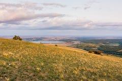 Панорама ландшафта захода солнца, холмы в золотом часе, малая деревня в долине, красивые цвета и облака Стоковое фото RF