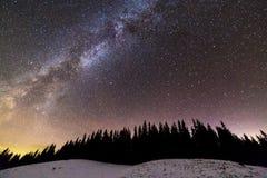 Панорама ландшафта ночи гор зимы Созвездие млечного пути яркое в темно-синем звездном небе над темными елевыми соснами стоковое изображение rf