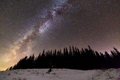 Панорама ландшафта ночи гор зимы Созвездие млечного пути яркое в темно-синем звездном небе над темными елевыми соснами стоковое изображение