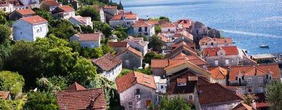 Панорама маленького города около моря, красных крыть черепицей черепицей крыш, зеленых цветов Стоковые Изображения
