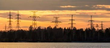 панорама, передающая линия на береге резервуара в конце дня, энергии Стоковые Фото