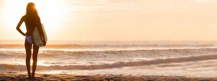 Панорама пляжа захода солнца серфера & Surfboard бикини женщины стоковая фотография