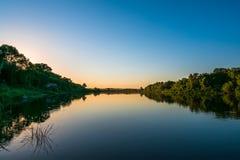 Панорама природы лета на заходе солнца, лесные деревья и река с отражением в воде, яркое спокойное и ослабляют предпосылку Стоковое Фото