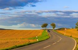Панорамный ландшафт красочных желт-зеленых холмов с земной дорогой, голубым небом и облаками Стоковая Фотография