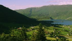 Панорамный взгляд города на горах покрыл древесные зелени в дне лета солнечном ветер Река Природа сток-видео